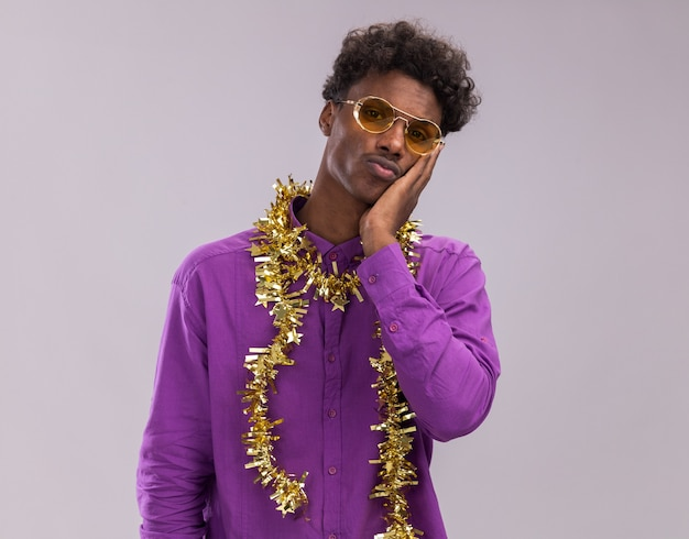Anxious young afro-american man wearing glasses with tinsel garland around neck looking at camera keeping hand on face isolated on white background with copy space