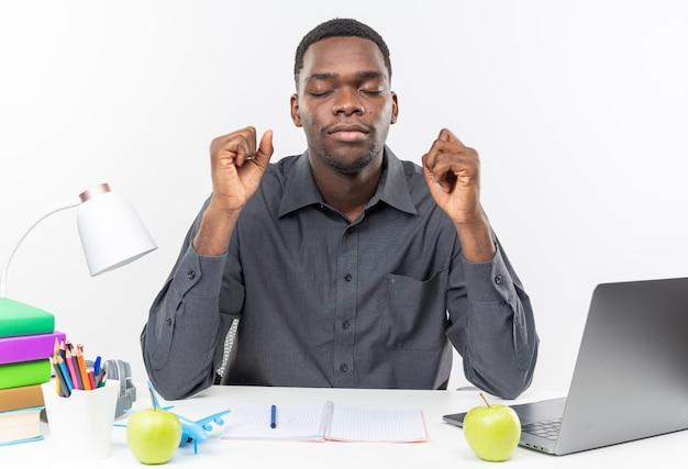 흰 벽에 주먹을 쥔 채 학교 도구를 들고 책상에 눈을 감고 앉아 있는 불안한 젊은 아프리카계 미국인 학생