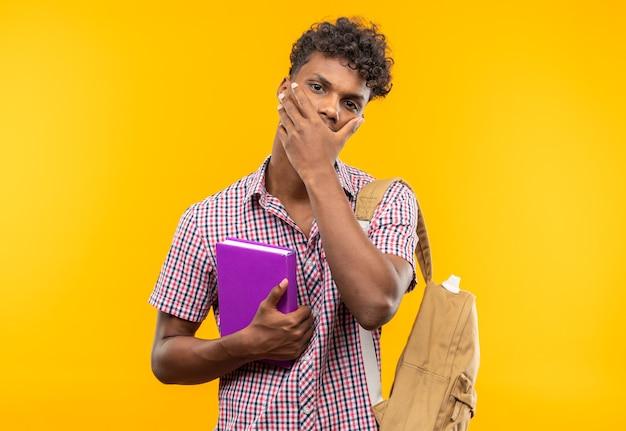 Ansioso giovane studente afroamericano con lo zaino che tiene il libro e si mette la mano sulla bocca