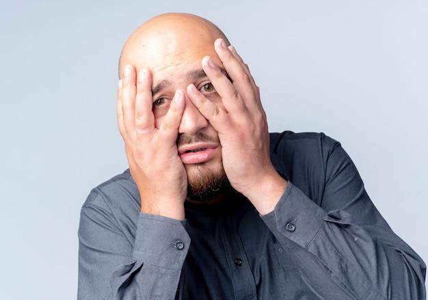Uomo calvo giovane ansioso della call center che mette le mani sul fronte che sembra isolato su bianco