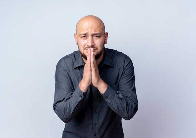 Uomo calvo giovane ansioso della call center che mette le mani nel gesto di preghiera isolato su bianco con lo spazio della copia