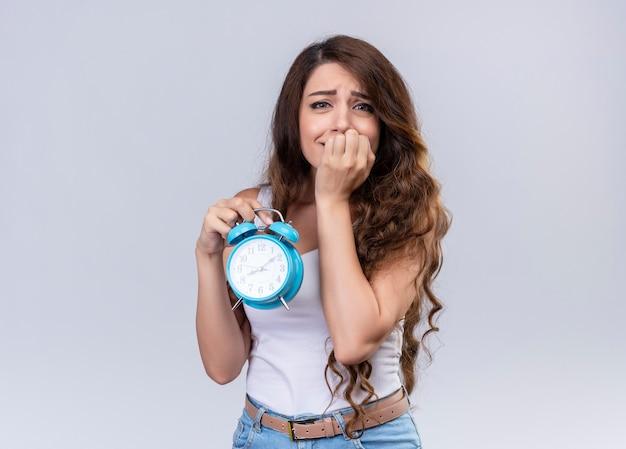 Тревожная молодая красивая девушка держит будильник и кладет руку в рот с копией пространства