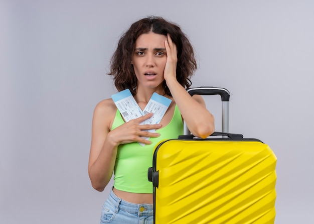 Anxious young beautiful traveler woman holding airplane tickets and suitcase on isolated white wall with copy space