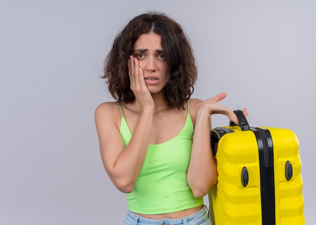 Anxious young beautiful traveler woman holding suitcase and putting hand on cheek on isolated white wall with copy space