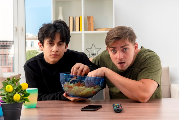Anxious young blonde and brunette handsome guys sit at table holding and eating bowl of chips inside living room
