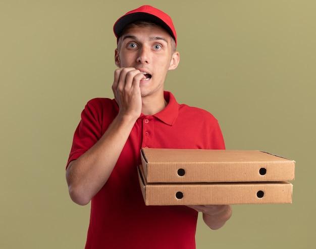 Ansioso giovane biondo consegna ragazzo morde le unghie e tiene scatole per pizza su verde oliva