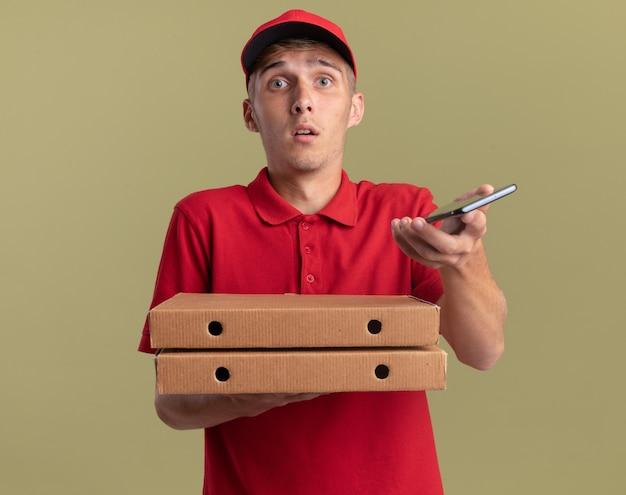 불안한 젊은 금발 배달 소년은 복사 공간이 있는 올리브 녹색 벽에 격리된 피자 상자와 전화를 들고 있습니다