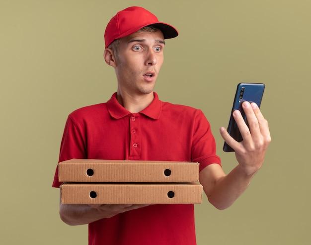 Il giovane ragazzo delle consegne biondo ansioso tiene le scatole della pizza e guarda il telefono