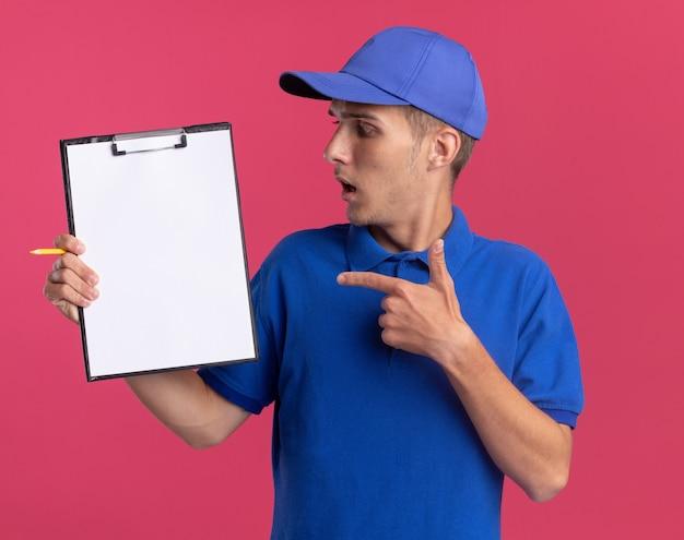 Il giovane ragazzo delle consegne biondo ansioso guarda e indica la lavagna per appunti isolata sulla parete rosa con lo spazio della copia