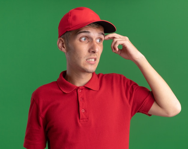 Il giovane ragazzo di consegna biondo ansioso mette il dito sulla tempia e guarda a lato sul verde
