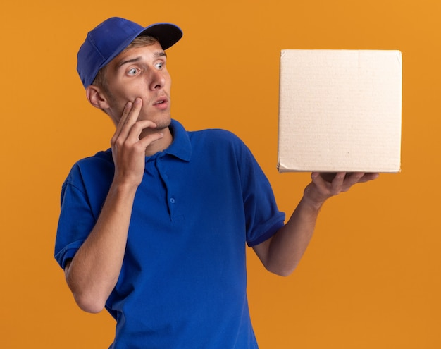 Обеспокоенный молодой блондин посыльный кладет руку на лицо, держа и глядя на картонную коробку, изолированную на оранжевой стене с копией пространства