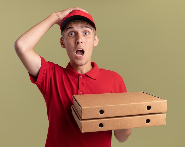불안한 젊은 금발 배달 소년 머리에 손을 넣고 올리브 그린에 피자 상자를 보유