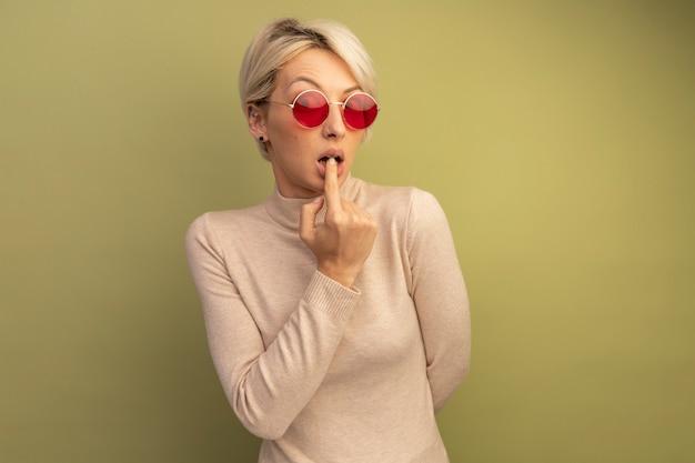 Ansiosa giovane ragazza bionda che indossa occhiali da sole tenendo la mano dietro la schiena mettendo il dito sul labbro