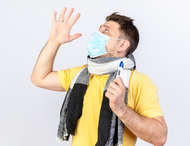 Anxious young blonde ill man wearing medical mask and scarf stands with raised hand holding thermometer and looking up isolated on white wall