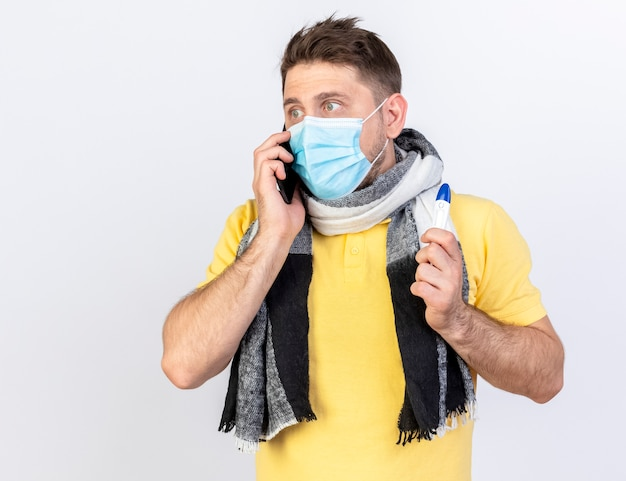 Anxious young blonde ill man wearing medical mask and scarf talks on phone and holds thermometer isolated on white wall