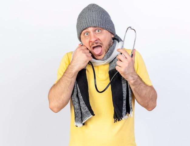 冬の帽子とスカーフを身に着けている気になる若い金髪の病気の男は、白い壁に隔離された聴診器を保持します