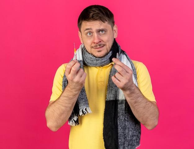 Взволнованный молодой блондин больной славянский мужчина в шарфе держит шприц и ампулу на розовом