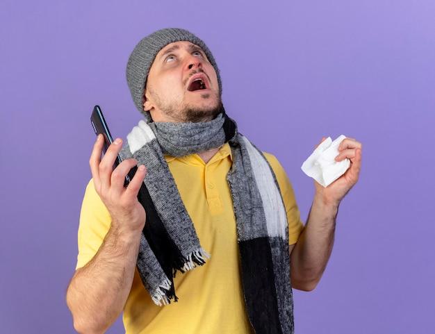 겨울 모자와 스카프를 착용하는 불안한 젊은 금발의 아픈 슬라브 남자가 조직을 보유하고 있습니다.