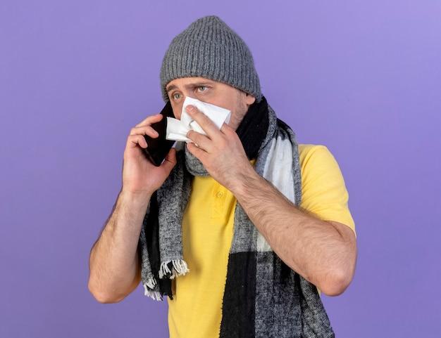 겨울 모자와 스카프를 착용하는 불안한 젊은 금발의 아픈 슬라브 남자가 전화로 이야기하는 코를 닦습니다.