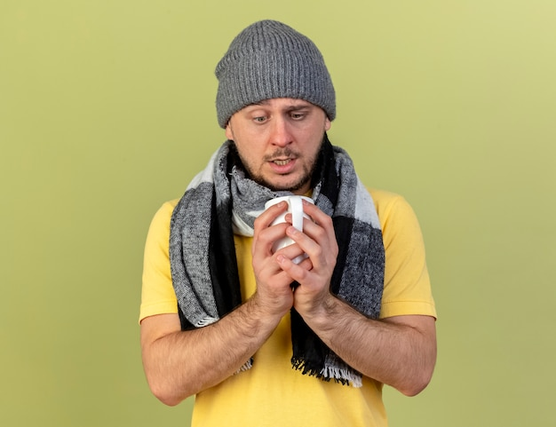 Il giovane uomo slavo malato biondo ansioso che porta il cappello e la sciarpa di inverno tiene