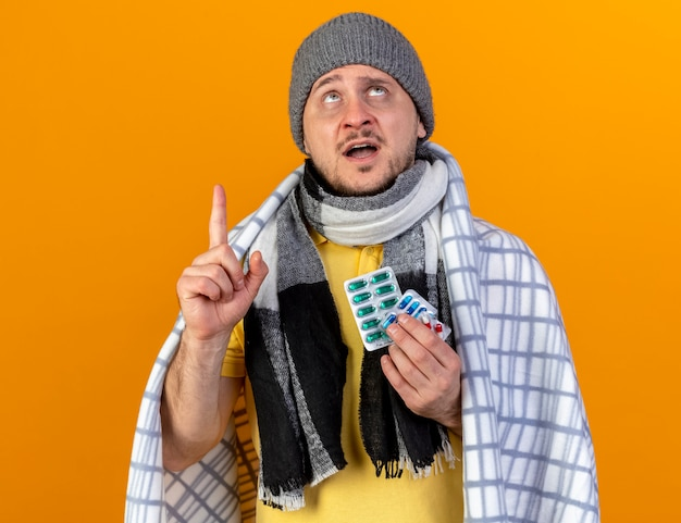 Ansioso giovane biondo slavo malato che indossa sciarpa e cappello invernale
