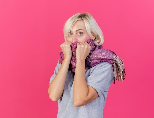 コピースペースとピンクの壁に分離されたスカーフを身に着けて保持している気になる若いブロンドの病気のスラブ女性