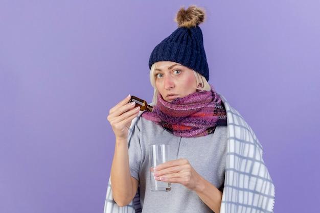 冬の帽子とスカーフを身に着けている気になる若い金髪の病気のスラブ女性