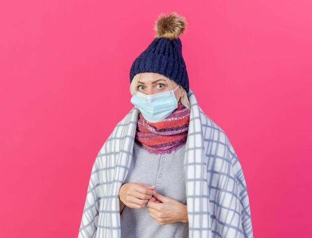 Ansiosa giovane bionda malata donna slava che indossa cappello invernale maschera medica e sciarpa avvolto in plaid tiene le mani insieme isolato sulla parete rosa con spazio di copia