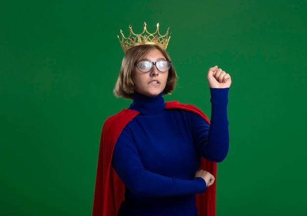 眼鏡と王冠を身に着けている赤いマントの気になる若いブロンドのスーパーヒーローの女性は、コピースペースで緑の壁に分離された拳を噛む前を噛んで