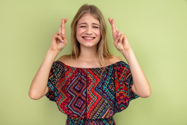 Ansiosa giovane donna bionda incrociando le dita