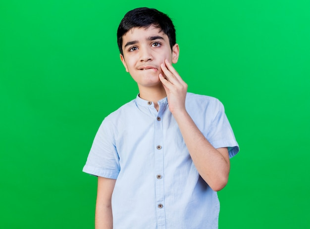 緑の壁に分離された唇を噛む顔に触れる正面を見て気になる少年