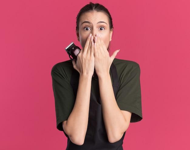 Обеспокоенная молодая брюнетка-парикмахер в униформе кладет руки на рот, держа машинку для стрижки волос на розовом