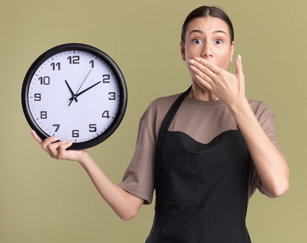 La giovane ragazza ansiosa del barbiere castana in uniforme mette la mano sulla bocca e tiene l'orologio isolato sulla parete verde oliva con lo spazio della copia
