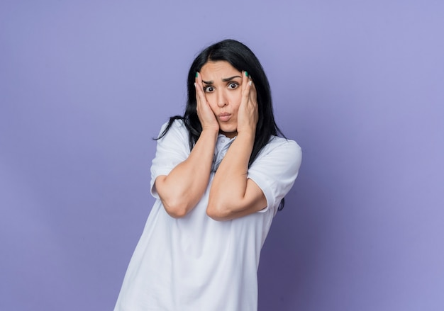 気になる若いブルネット白人の女の子は紫色の壁に分離された両手で顔を保持