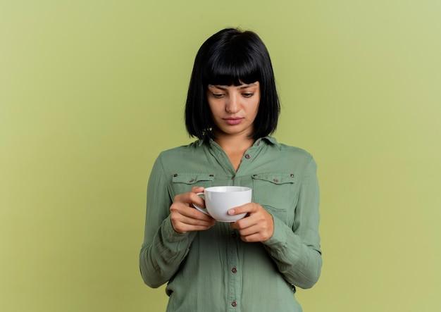 La giovane ragazza caucasica castana ansiosa tiene ed esamina la tazza