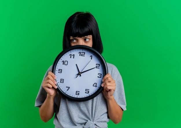La giovane ragazza caucasica castana ansiosa tiene ed esamina il lato sopra l'orologio
