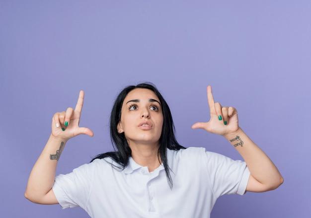 気になる若いブルネット白人の女の子は、紫色の壁に分離された両手で指