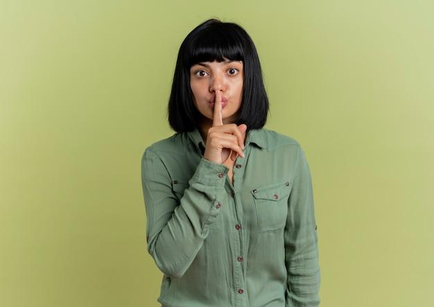 Ansiosa giovane ragazza caucasica bruna mette il dito sulla bocca gesticolando silenzio segno tranquillo