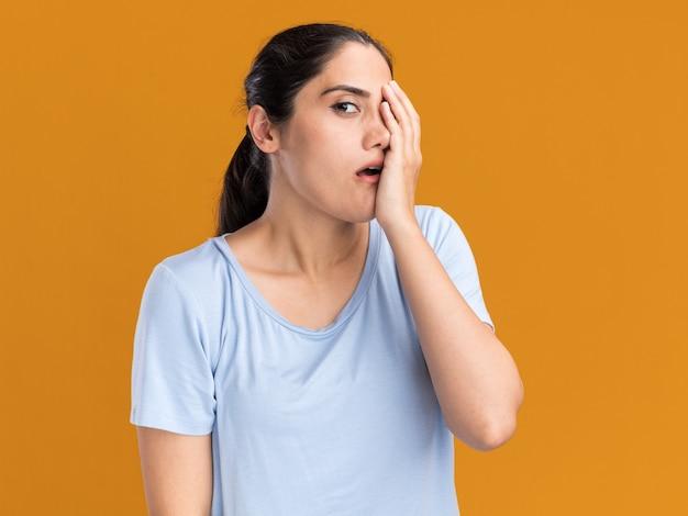 Ansiosa giovane ragazza caucasica bruna mette la mano sul viso e guarda la telecamera su arancione