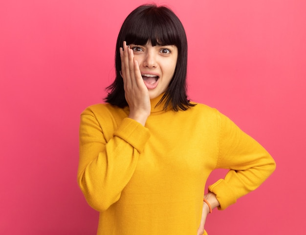 Ansiosa giovane ragazza caucasica bruna mette la mano sul viso e guarda la telecamera sul rosa