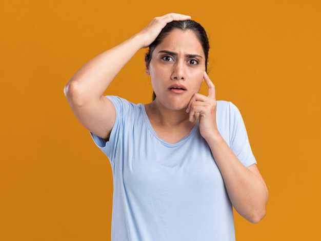 La giovane ragazza caucasica castana ansiosa mette la mano sulla testa ed esamina la macchina fotografica sull'arancio