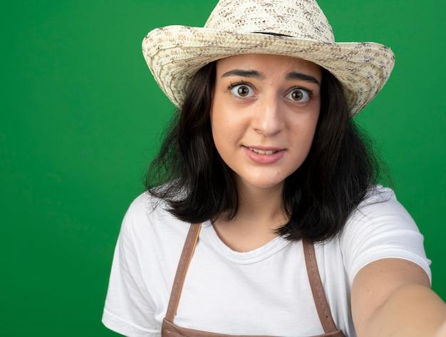Взволнованная молодая брюнетка женщина-садовник в оптических очках и униформе в садовой шляпе держит и смотрит на переднюю часть, изолированную на зеленой стене