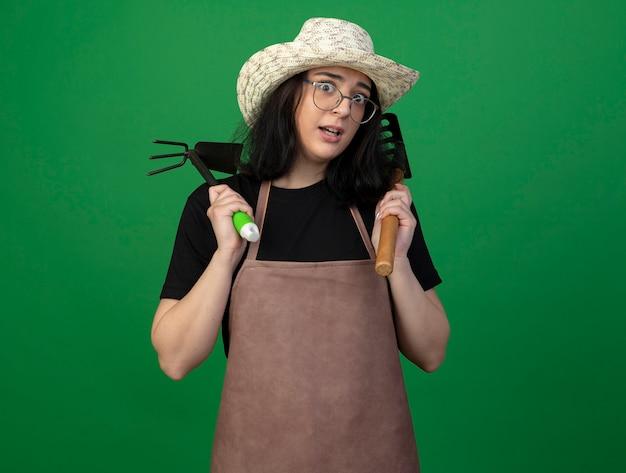 Взволнованная молодая брюнетка женщина-садовник в оптических очках и униформе в садовой шляпе держит грабли и мотыгу, изолированные на зеленой стене