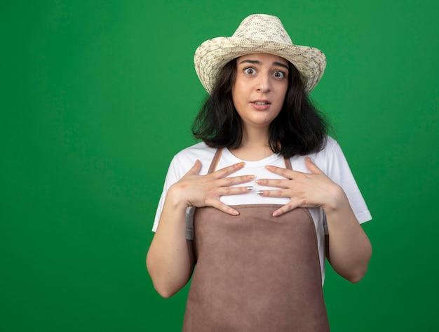 Взволнованная молодая брюнетка женщина-садовник в оптических очках и униформе в садовой шляпе кладет руки на грудь, изолированную на зеленой стене