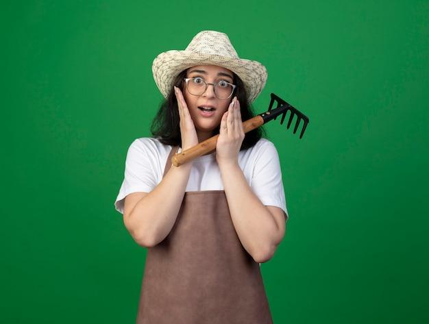 Взволнованная молодая брюнетка женщина-садовник в оптических очках и униформе в садовой шляпе кладет руки на лицо, держа грабли на зеленой стене