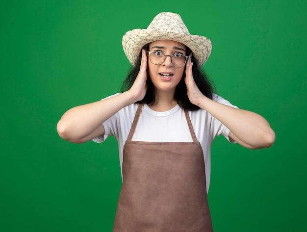 Взволнованная молодая брюнетка женщина-садовник в оптических очках и униформе в садовой шляпе кладет руки на лицо, изолированное на зеленой стене
