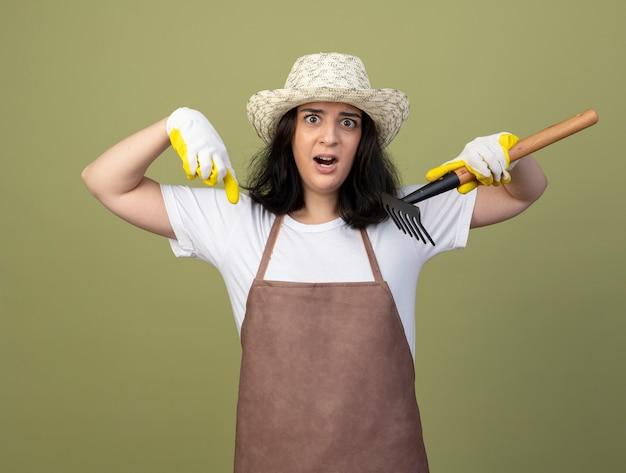 Обеспокоенная молодая брюнетка женщина-садовник в униформе в садовой шляпе и перчатках держит грабли и указывает вниз, изолированную на оливково-зеленой стене