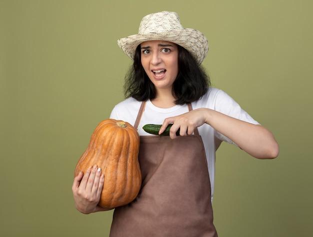 Взволнованная молодая брюнетка женщина-садовник в униформе в садовой шляпе держит тыкву и огурец, изолированные на оливково-зеленой стене