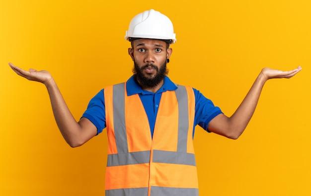 안전 헬멧을 쓴 불안한 젊은 건축업자 남자는 복사 공간이 있는 주황색 벽에 격리되어 손을 벌리고 있습니다