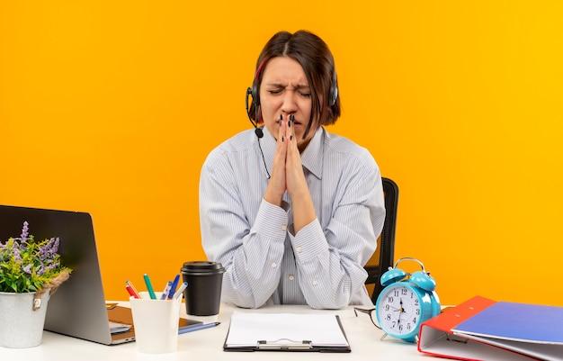 Тревожная молодая девушка из колл-центра в наушниках сидит за столом, сложив руки в жесте молитвы с закрытыми глазами, изолированными на оранжевом